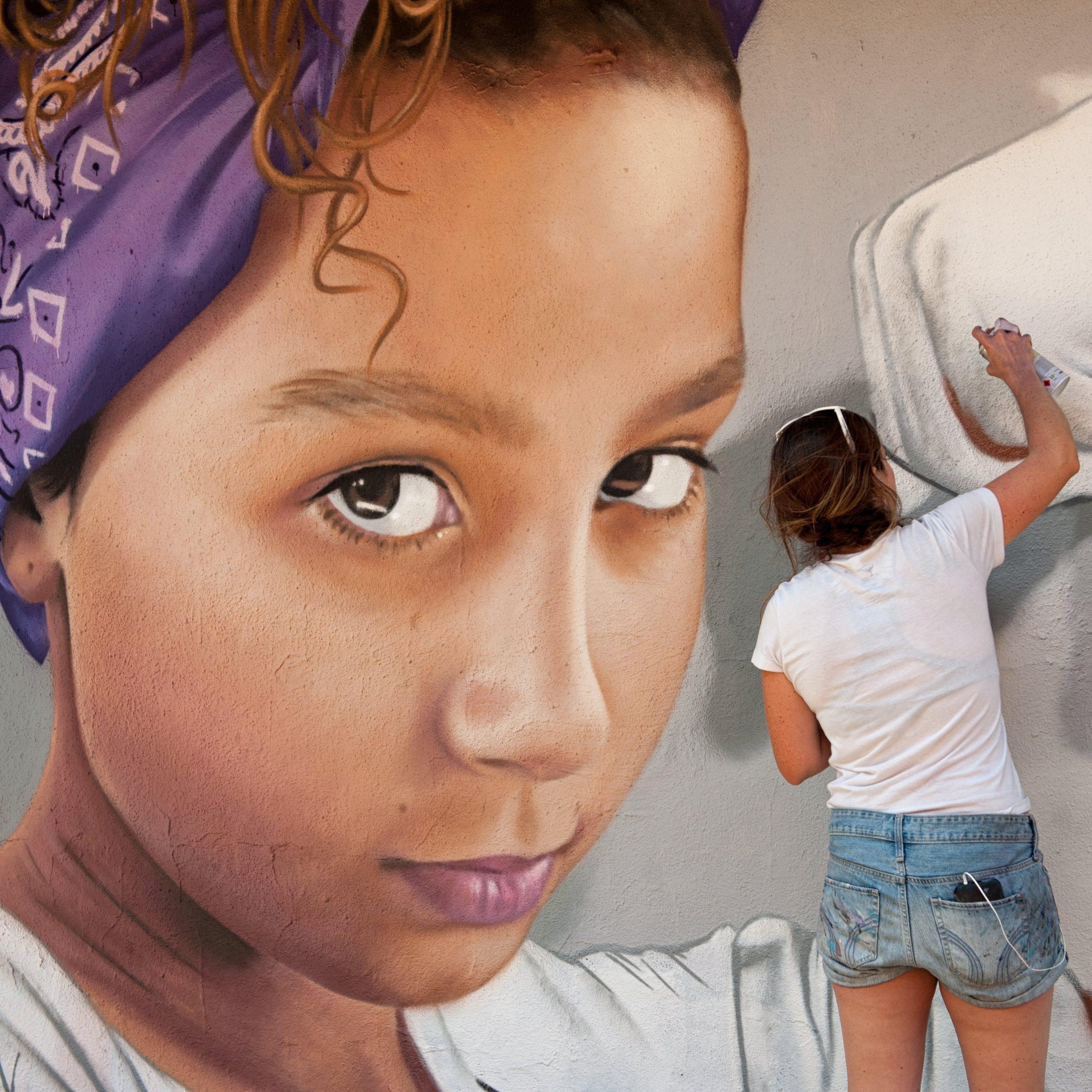 Kunstenaar werkt aan muurschildering